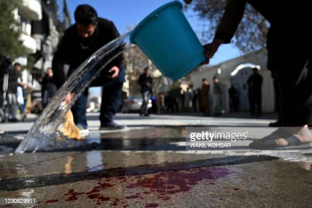 Residents wash a road following gunmen shot dead two Afghan women judges working for the Supreme Court, in Kabul on January 17, 2021. - Gunmen shot...