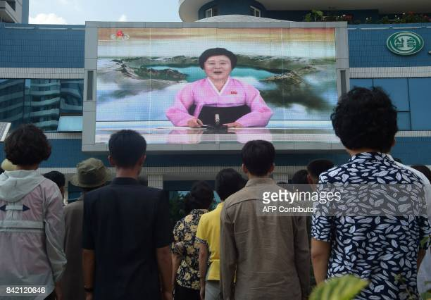 TOPSHOT Residents watch a big video screen on Mirae Scientists Street in Pyongyang showing newsreader Ri ChunHee as she announces the news that the...