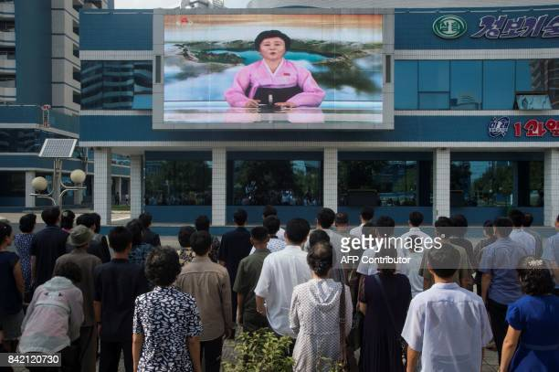 Residents watch a big video screen on Mirae Scientists Street in Pyongyang showing newsreader Ri ChunHee as she announces the news that the country...