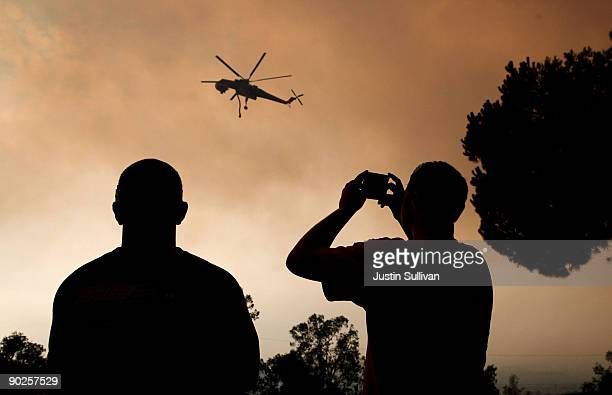 Residents watch a firefighting helicopter fly overhead September 1 2009 in Tujunga California The out of control Station Fire has burned more than...