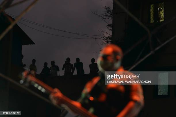 Residents watch a music band formed by Sri Lankan Army personnel as they play outside a housing complex during a governmentimposed nationwide...