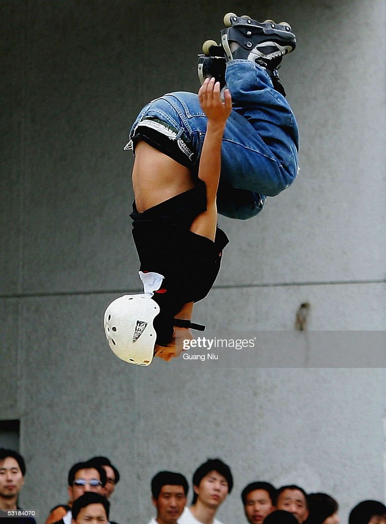 Residents watch a participant in the Extreme Sports Games on July 2, 2005 in Beijing, China. Local authorities are gearing up to promote sporting activities in the city as the 2008 Beijing Olympics is approaching.