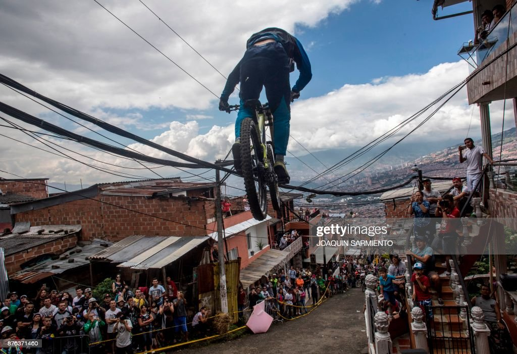 TOPSHOT - Residents watch as a downhill rider competes during the Urban Bike Inder Medellin race final at the Comuna 1 shantytown in Medellin, Antioquia department, Colombia on November 19, 2017. /