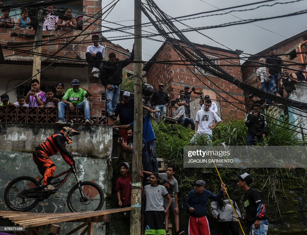 Residents watch as a downhill rider competes during the Urban Bike Inder Medellin race final at the Comuna 1 shantytown in Medellin, Antioquia department, Colombia on November 19, 2017. /