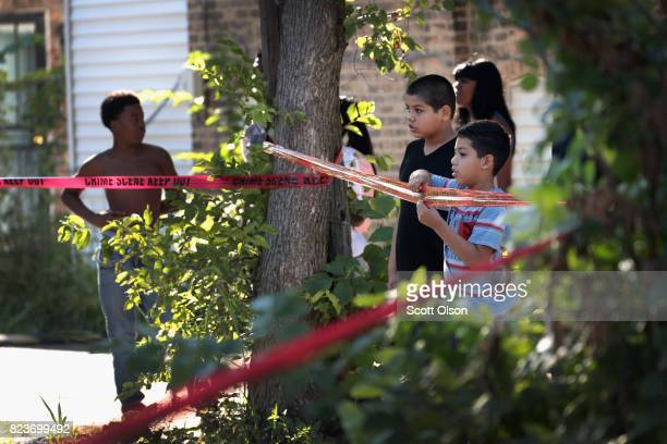 Residents watch as Chicago Police SWAT team members surround a house in the Humboldt Park neighborhood where they believe a man responsible for a...