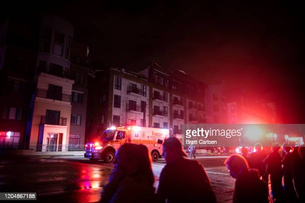 Residents watch as emergency crews attend to a tornado damaged apartment building on Jefferson St in Nashville TN on March 3 2020 in Nashville...
