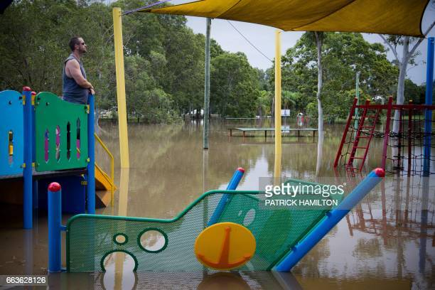 Residents watch as floodwaters caused by Cyclone Debbie recede in the town of Beenleigh on April 2 2017 Rising floods continued to plague parts of...