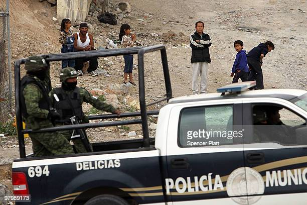 Residents watch as military police stand guard at the scene of a murder on March 23 2010 in Juarez Mexico Secretary of State Hillary Rodham Clinton...