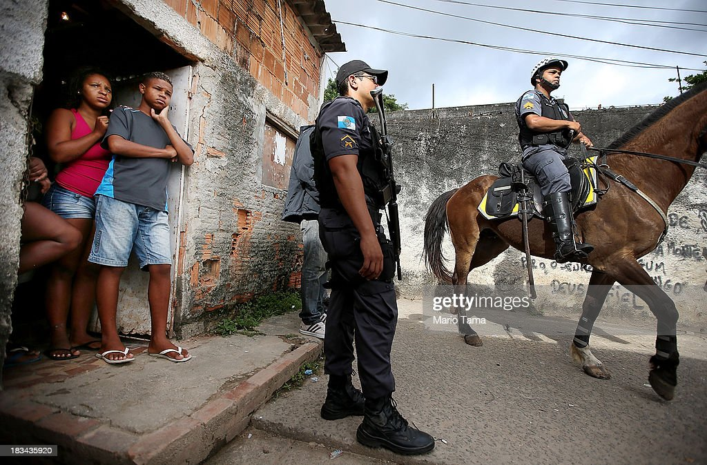 Residents (L) watch as police on horseback and patrol during a 'pacification' operation in the favela complex of Lins de Vasconcelos, in the North Zone, on October 6, 2013 in Rio de Janeiro, Brazil. The favela complex, or shanty town, was previously controlled by drug traffickers and will now be occupied by the city's 35th UPP or 'Police Pacification Unit'. The favela pacifications are occurring amid Rio de Janeiro's efforts to improve security ahead of the 2014 FIFA World Cup and 2016 Olympic Games.