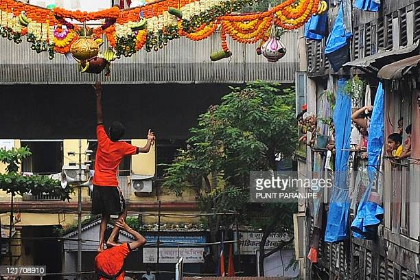 Residents watch from their windows as an Indian devotee reaches for a suspended clay pot after climbing a human pyramid to break the 'dahihandi' in...