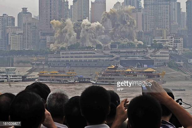 Residents watch on as The Three Gorges Hotel and the 32storey passenger terminal of Chongqing port are toppled in a controlled explosion to make way...