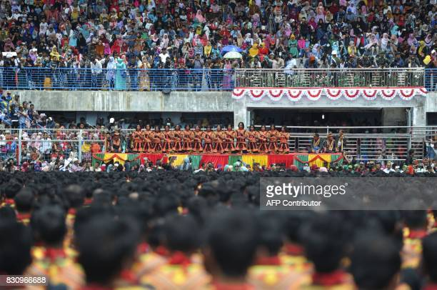 Residents watch participants take part in a mass traditional Saman dance performance in the Gayo Lues highland district in Aceh on Indonesia's...