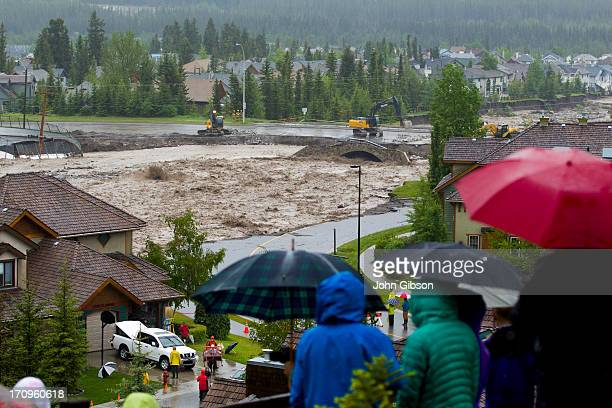 Residents watch the flooding Cougar Creek as it takes out Eagle Terrace Road and nears the top of the Elk Run Blvd Bridge June 20 2013 in Canmore...