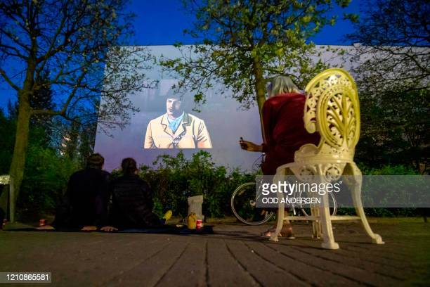 "Residents watch the movie ""Loving Vincent"" projected on the wall of a neighbouring building from their front garden in Berlin's Kreuzberg district on..."