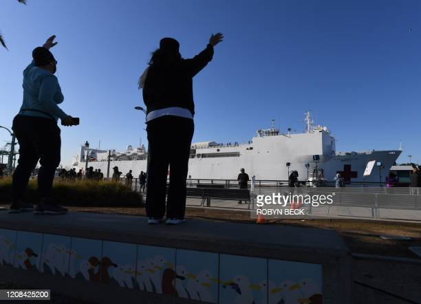 Residents wave as the US Navy hospital ship Mercy arrives March 27 2020 at the Port of Los Angeles to help local hospitals amid the growing...