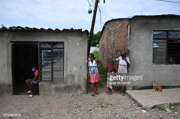 Residents wear face masks as a preventive measure against the spread of the novel coronavirus outside their homes at Aguablanca district in Cali,...