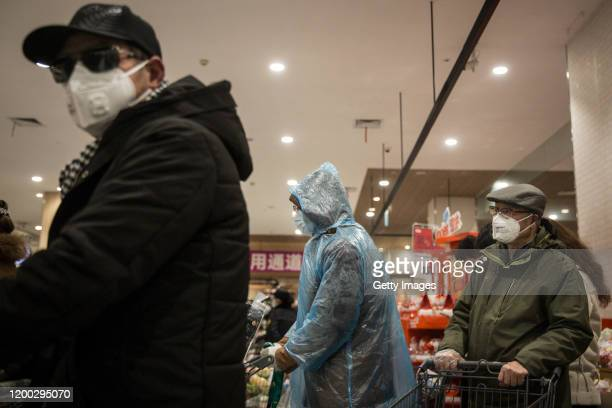 Residents wear protective clothes and mask as they line up to pay in the supermarket on February 12, 2020 in Wuhan, Hubei province, China. Flights,...
