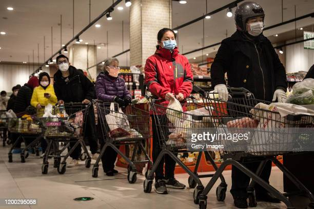 Residents wear protective masks as they line up in the supermarket on February 12, 2020 in Wuhan, Hubei province, China. Flights, trains and public...