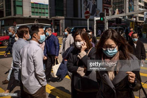 Residents wear surgical mask as they cross a street in a shopping district on January 31 2020 in Hong Kong China Hong Kong faces supply issues of...
