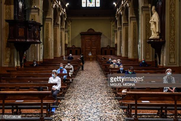 Residents wearing a face mask attend a morning mass at San Biagio and Santa Maria Immacolata church on May 20, 2020 in Codogno, southeast of Milan,...