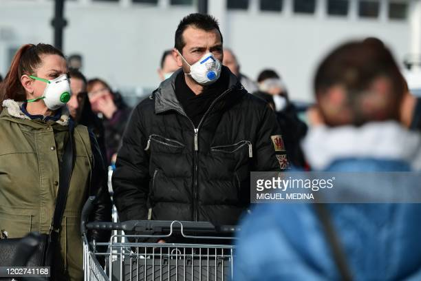 Residents wearing a respiratory mask wait to be given access to shop in a supermarket in small groups of forty people on February 23, 2020 in the...