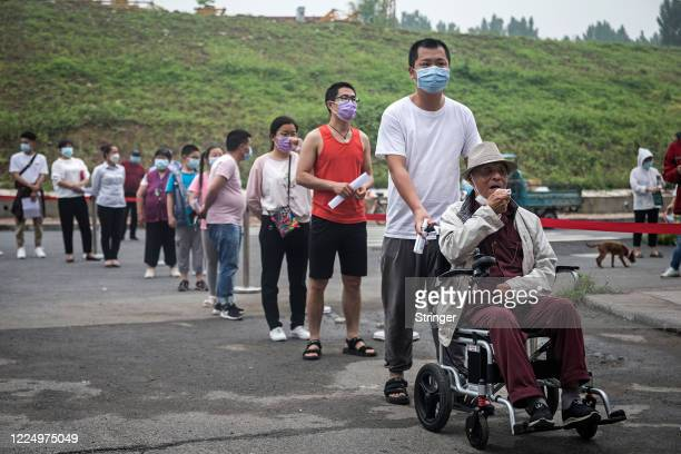 Residents wearing face masks wait in line for nucleic acid testing at a residential community on May 15 2020 in Wuhan Hubei China The city plans to...