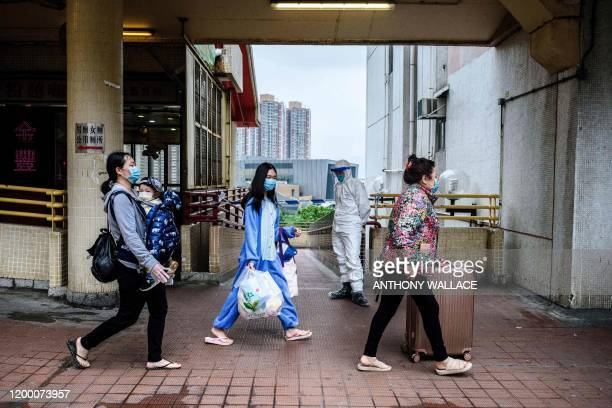 Residents wearing face masks walk outside Hong Mei House as a police officer wearing protective gear stands in front of a cordon at the Cheung Hong...