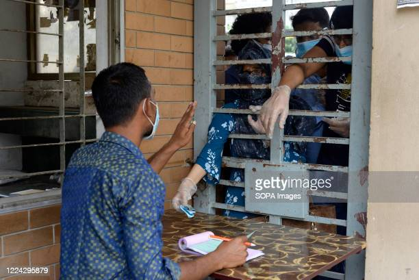 Residents wearing facemasks collect tickets from an employee for Covid-19 testing. Mugda Medical College and Hospital employees collect samples from...