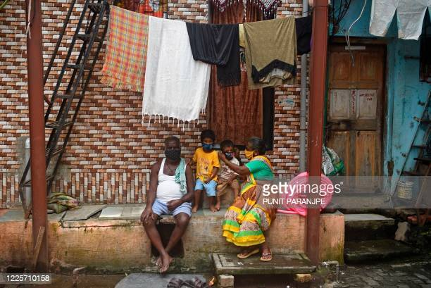 Residents wearing facemasks sit outside their house during a door-to-door medical screening inside Dharavi slums to fight against the spread of the...