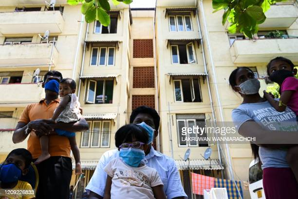 TOPSHOT Residents wearing facemasks watch a music band formed by Sri Lankan Army personnel play outside a housing complex during a governmentimposed...