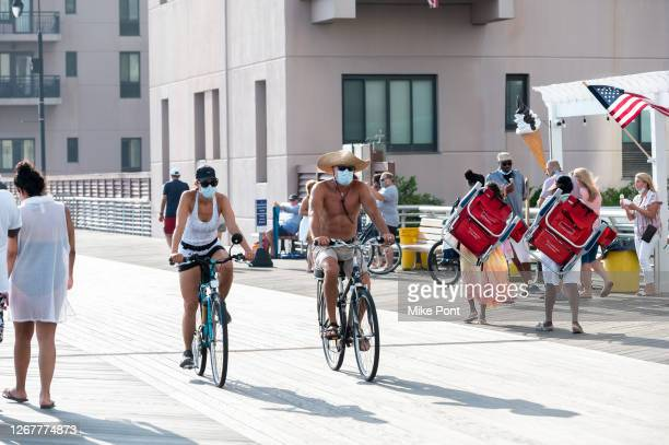 Residents wearing protective face masks ride bicycles on the boardwalk during Phase 4 of re-opening following restrictions imposed to slow the spread...