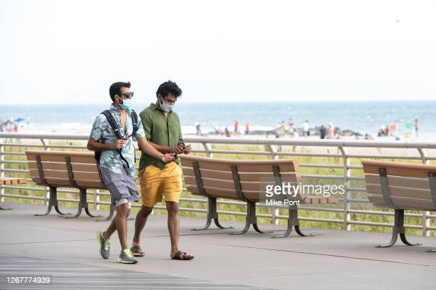 Residents wearing protective face masks walk on the beach and boardwalk during Phase 4 of re-opening following restrictions imposed to slow the...