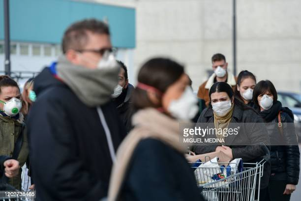 Residents wearing respiratory mask wait to be given access to shop in a supermarket in small groups of forty people on February 23, 2020 in the small...