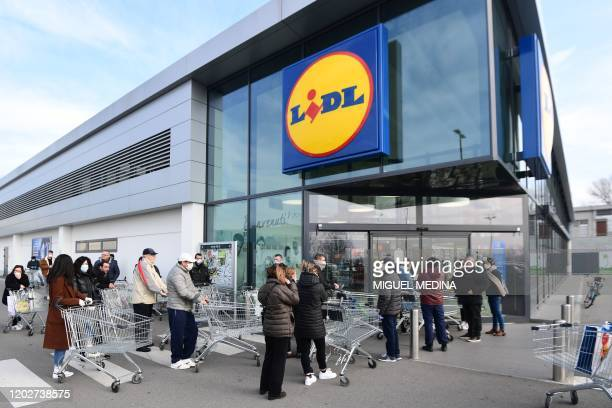 Residents wearing respiratory mask wait to be given access to shop in a supermarket in small groups of forty people on February 23 2020 in the small...