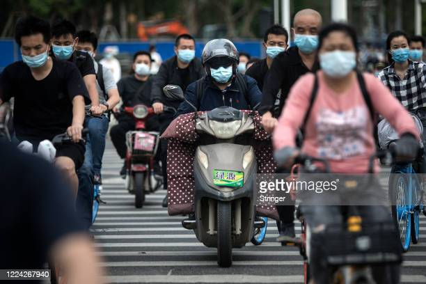 Residents wears face masks while riding their bicycles on May 11, 2020 in Wuhan, China. The government has begun lifting outbound travel restrictions...