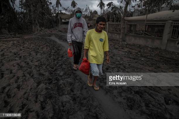 Residents who briefly returned home to retrieve belongings walk along a road covered in volcanic ash from Taal Volcano's eruption on January 14 2020...