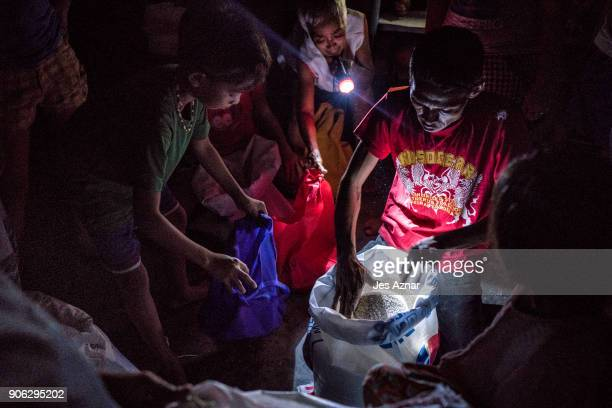 Residents who evacuated from Mayon volcano's eruption getting a ration of rice inside a public school on January 17 2018 in Legazpi Albay Philippines...