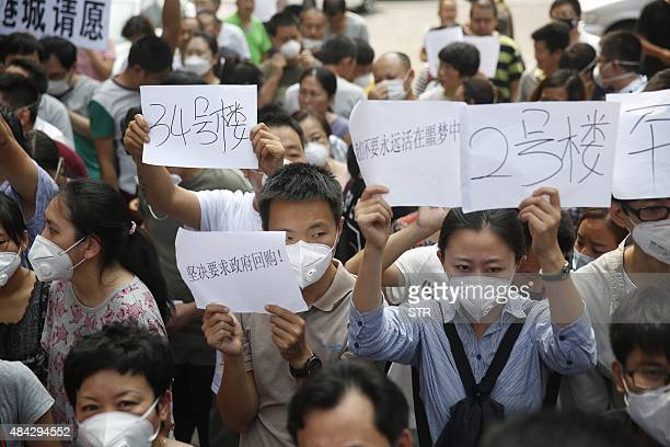 Residents whose homes were destroyed in the explosion at a chemical warehouse last week protest outside the hotel where authorities are holding a...