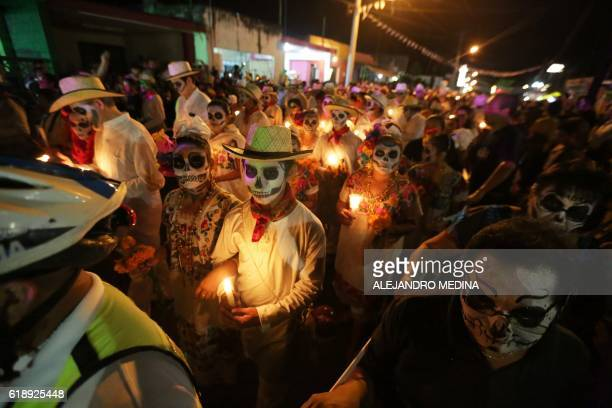 Residents with painted faces and holding candles participate in El Paseo de Las Almas The Walk of Souls during a Day of the Dead festival in Merida...