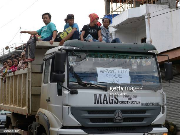Residents with their belongings ride a government truck as they evacuate from Marawi on the southern island of Mindanao on May 26 as the battle...