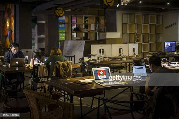 Residents work at their laptop computers as a cartoon illustration asking for investments is displayed on a laptop screen inside a You community in...