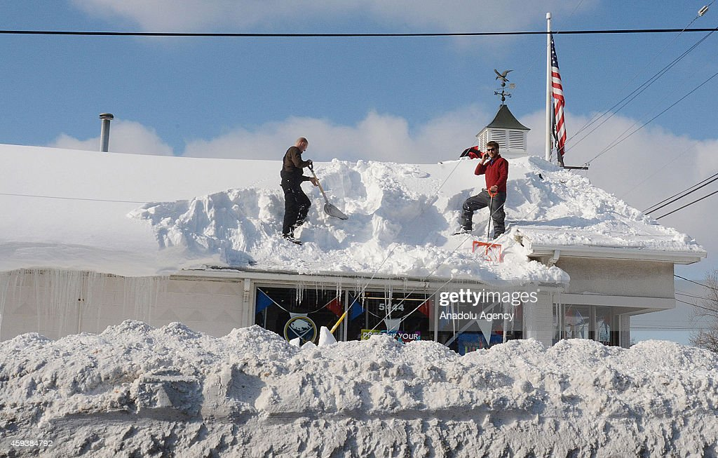 A residents work to remove snow from the roof on November 21, 2014 in Buffalo, New York as the death toll attributed to Buffalo snow rises to 13. A brutal blast of Arctic air triggered a lake-effect storm and snow in the states of New York, Ohio, Michigan, Wisconsin and Pennsylvania.