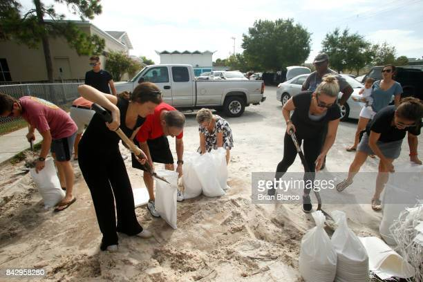 Residents work together to fill sandbags for each other at Bobby Hicks Park as residents prepare ahead of Hurricane Irma on September 5 2017 in Tampa...