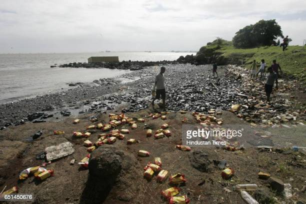 Residue of fuel oil and packets of food packets which were packed in the containers that fell from the vessel MSC Chitra strewn around near Rajbunder...