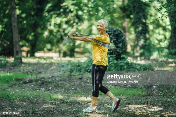 resistance band walking exercise. mature woman doing strength workout with elastic resistance band - belgrade serbia stock pictures, royalty-free photos & images