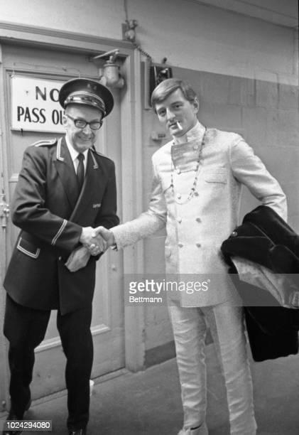 "Resplendent in yellow lamb negru suit, Red Sox player Ken ""The Hawk"" Harrelson , shakes hands with Boston Garden press gate usher Tom Tweedle...."