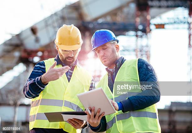 responsible manager having discussion on construction site - bridge built structure stock pictures, royalty-free photos & images