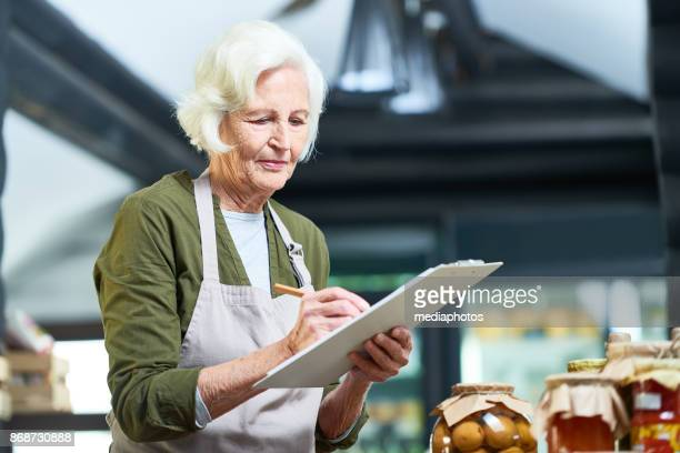 responsible senior entrepreneur running small business - working seniors stock pictures, royalty-free photos & images