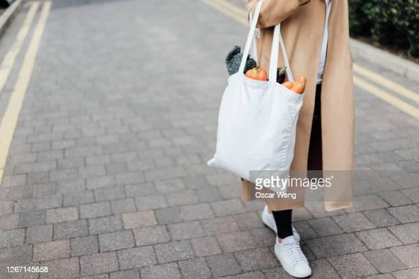 responsible shopper using reusable shopping bag for groceries - tragetasche oder tragebeutel stock-fotos und bilder