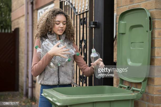 responsible teenager putting plastic bottles in recycle bin - green colour stock pictures, royalty-free photos & images